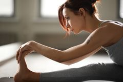 Young sporty woman doing yoga stretching exercise sitting in gym near bright windows Stock Image