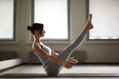 Young sporty woman doing yoga stretching exercise sitting in gym near bright windows Royalty Free Stock Images