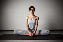 Young sporty woman doing yoga stretching exercise sitting in gym near bright windows Stock Photo
