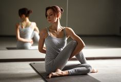 Young sporty woman doing yoga stretching exercise sitting in gym near bright windows Royalty Free Stock Photography