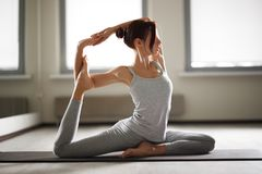 Young sporty woman doing yoga stretching exercise sitting in gym near bright windows Stock Photography