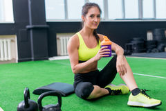 Young sporty woman drinking water in gym, holding bottle, having break Royalty Free Stock Images