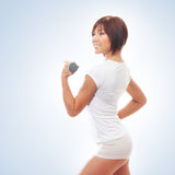Young sporty woman with a dumbbell over blue background Royalty Free Stock Images
