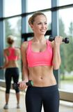 Young sporty woman with dumbbells flexing biceps stock images
