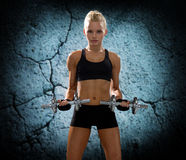Young sporty woman with dumbbells flexing biceps Royalty Free Stock Image