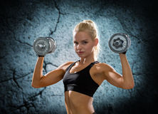 Young sporty woman with dumbbells flexing biceps Stock Photo