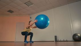 Young Sporty Woman is Doing Squats with Fitball at Hands in Training Gym. Young Sporty Woman is Exercising by Doing Squats with Fitball at Hands in Training Gym stock video footage