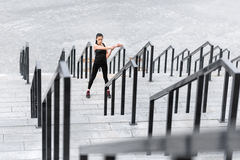 Young sporty woman exercising and stretching on stadium stairs Royalty Free Stock Image
