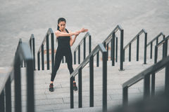 Young sporty woman exercising and stretching on stadium stairs Stock Image