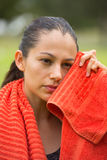 Young sporty woman exhausted with towel outdoor Stock Photo