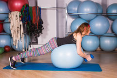 Young sporty woman in gym doing fitness exercice with blue ball Royalty Free Stock Photos