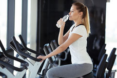 Young sporty woman in gym drinking water Stock Image