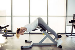 Young sporty woman in gym. Hyperextension exercise. Stock Photography