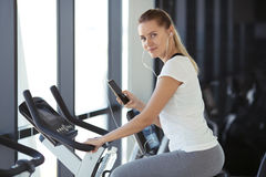 Young sporty woman in gym listen music from smartphone Stock Photo