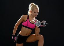 Young sporty woman with heavy steel dumbbell Royalty Free Stock Images
