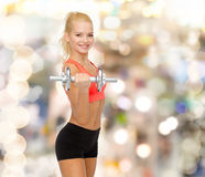 Young sporty woman with heavy steel dumbbell Royalty Free Stock Image