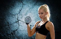 Young sporty woman with heavy steel dumbbell Stock Image
