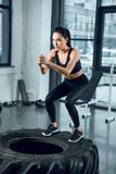 young sporty woman jumping on workout wheel royalty free stock image