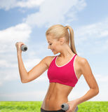 Young sporty woman with light dumbbells outdoors Royalty Free Stock Images
