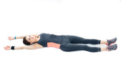 Young sporty woman lying on the floor and stretching Stock Photo