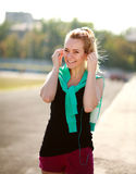Young sporty woman in the morning with headphones on treadmill Stock Images