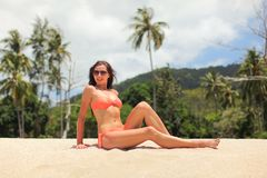 Young sporty woman in orange bikini and sunglasses, sitting on the sand near beach, palm trees behind her royalty free stock photos