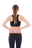 Young sporty woman with pain in her back isolated on white. Background stock images