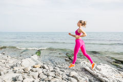 Young sporty woman in pink uniform outdoors. Fitness girl running on beach Stock Photos