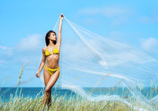 Young, sporty woman posing with blowing silk Royalty Free Stock Photos