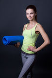 Young sporty woman posing with yoga mat over grey Royalty Free Stock Image