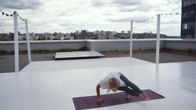 Young sporty woman is practicing handstand yoga pose - Astavakrasana at roof. In slow motion. Flexible girl is practicing yoga eight angle pose outdoors in stock footage