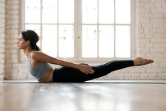 Young sporty woman practicing yoga, doing Double Leg Kicks exerc. Ise, Salabhasana pose, working out, wearing sportswear, pants and top, indoor full length stock photography