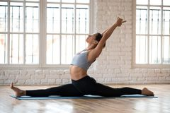 Young sporty woman practicing yoga, doing Monkey God exercise. Splits, Hanumanasana pose, working out, wearing sportswear, pants and top, indoor full length stock photography