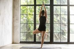 Young sporty woman in Vrksasana pose, window background Stock Photography