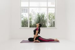 Young sporty woman practicing yoga near the window.  stock photography