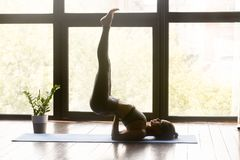 Young sporty woman practicing yoga in Viparita Karani pose. Young sporty woman practicing yoga, doing exercise, Viparita Karani pose, working out, wearing royalty free stock photos