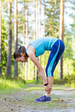 Young sporty woman preparing to run in forest. Stock Images