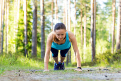 Young sporty woman preparing to run in forest. Stock Photos