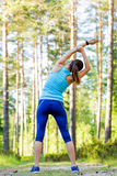Young sporty woman preparing to run in forest. Royalty Free Stock Images