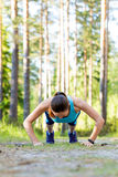 Young sporty woman preparing to run in forest. Stock Image