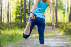 Young sporty woman preparing to run in forest. Royalty Free Stock Photography