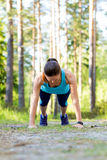 Young sporty woman preparing to run in forest. Royalty Free Stock Image