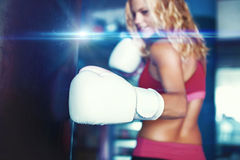 Young sporty woman punching into heavy bag graded. Young sporty woman punching into heavy bag in gym stock photo