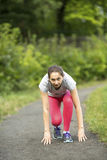 Young sporty woman ready to start running in the park in sunshine on beautiful summer day. Stock Photo
