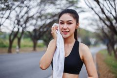 Young sporty woman resting and wiping her sweat with a towel aft Stock Images