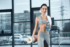young sporty woman with rolled yoga mat and water stock images