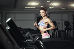 Young sporty woman run on machine in the gym Royalty Free Stock Images