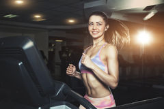 Young sporty woman run on machine in the gym royalty free stock image