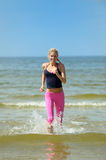 Young sporty woman running on the beach Stock Photography