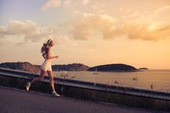 Young sporty woman running outdoor at sunset. Royalty Free Stock Photos